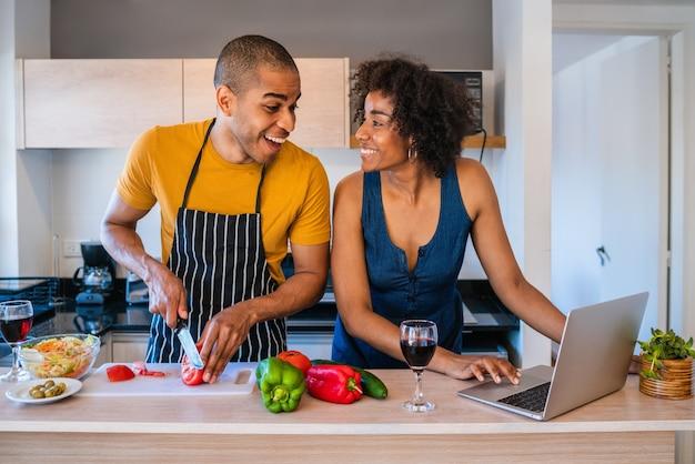Portret van jonge latijns-paar met behulp van een laptop tijdens het koken in de keuken thuis. relatie-, kook- en levensstijlconcept. Premium Foto