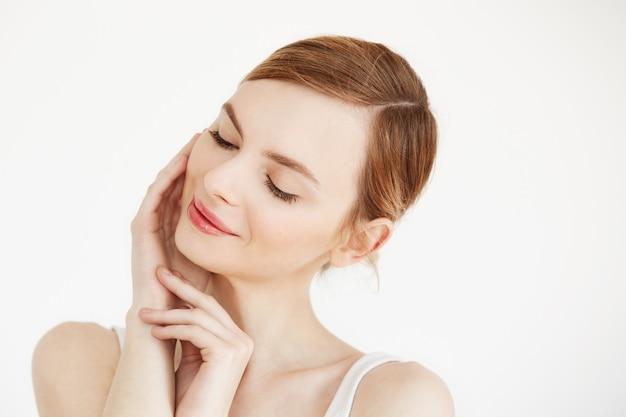 Portret van jonge mooi meisje glimlachend met gesloten ogen aanraken gezicht. gezichtsbehandeling. schoonheidskosmetiek en huidverzorging. Gratis Foto