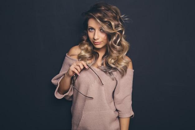 Portret van jonge mooie blond-haired trendy glazen en vrijetijdskleding dragen en het stellen over zwarte achtergrond Gratis Foto