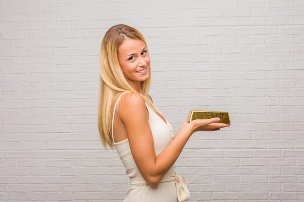 Portret van jonge mooie blonde vrouw tegen een bakstenen muur die iets met handen houdt, die een product toont, glimlachend en vrolijk, die een denkbeeldig voorwerp aanbiedt. een goudstaaf houden. Premium Foto