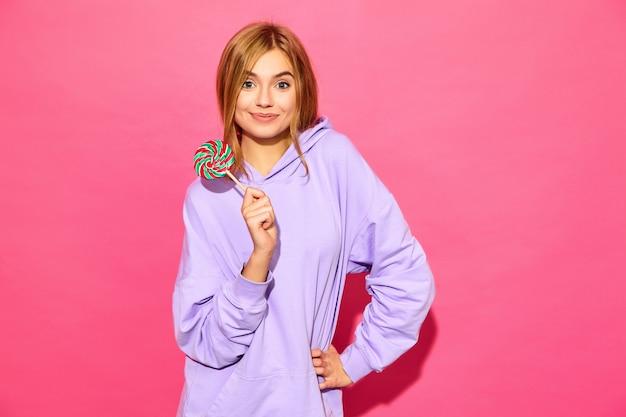 Portret van jonge mooie glimlachende hipster vrouw in trendy zomer hoodie. het sexy onbezorgde vrouw stellen dichtbij roze muur. positief model met lolly Gratis Foto