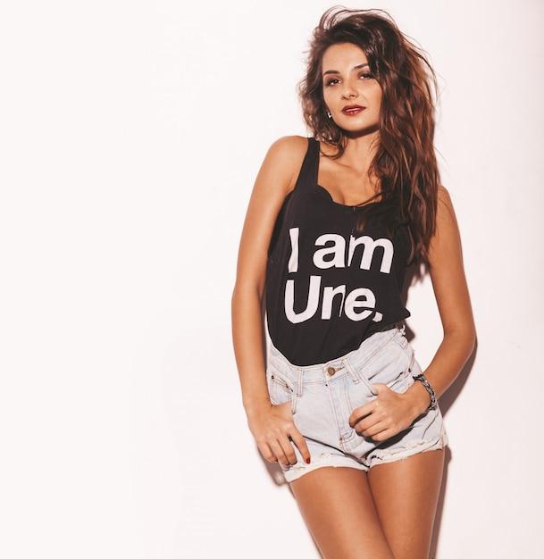Portret van jonge mooie hipster meisje in trendy zomer zwart t-shirt en jeans shorts. sexy onbezorgde die vrouw op wit wordt geïsoleerd. donkerbruin model met make-up en kapsel Gratis Foto