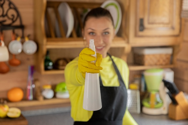 Portret van jonge mooie huisvrouw in zwarte schort die zich met keuken schonere nevel bevindt Premium Foto
