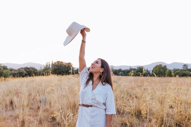 Portret van jonge mooie kaukasische vrouw die in openlucht bij zonsondergang op een geel gebied loopt. draagt een moderne hoed en glimlacht. geluk concept Premium Foto