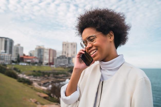 Portret van jonge mooie latijns-vrouw praten over de telefoon buitenshuis. communicatie concept. Gratis Foto