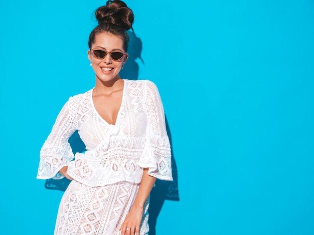 Portret van jonge mooie sexy glimlachende vrouw met lijkenetende kapsel. trendy meisje in casual zomer witte hipster pak kleding in zonnebril. heet model dat op blauw wordt geïsoleerd Gratis Foto