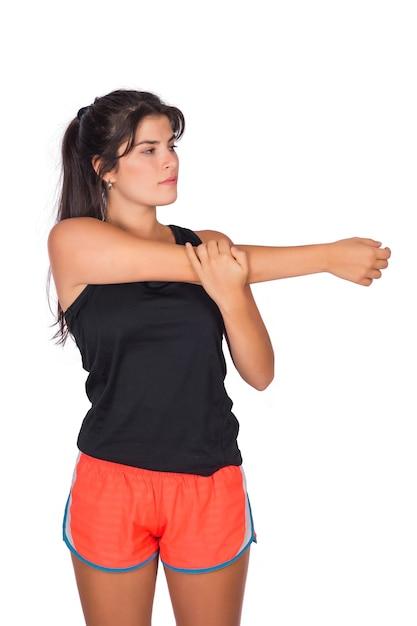 Portret van jonge mooie sportvrouw die sportkleren draagt en vóór oefening in studio rekt. sport en lifestyle concept. Gratis Foto