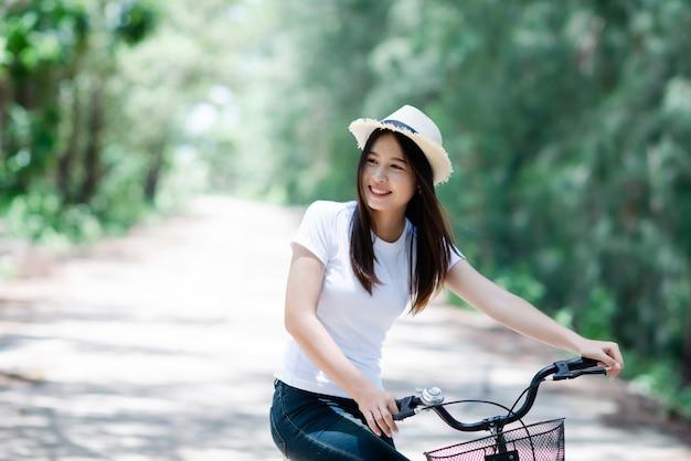Portret van jonge mooie vrouw die een fiets in een park berijdt. Gratis Foto