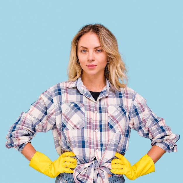 Portret van jonge mooie vrouw die gele handschoenen draagt die camera bekijken Gratis Foto