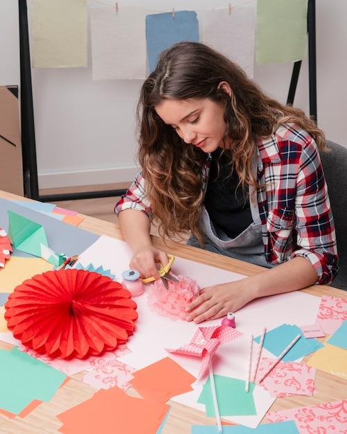 Portret van jonge mooie vrouw die origamidocument bloem maakt Gratis Foto