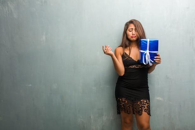 Portret van jonge mooie vrouw, gekleed in een jurk tegen een muur verdrietig en depressief Premium Foto