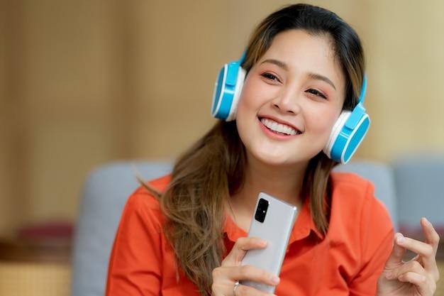 Portret van jonge mooie vrouw genieten van de muziek met smileygezicht zittend in creatieve kantoor of café Premium Foto