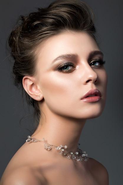 Portret van jonge mooie vrouw met bruids make-up en kapsel. moderne smokey eyes make-up Premium Foto