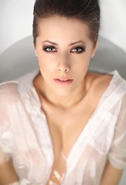 Portret van jonge mooie vrouw met kort haar die in bad in wit mannenoverhemd genieten van wat betreft lippen Gratis Foto
