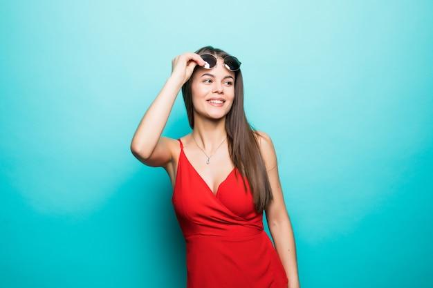 Portret van jonge mooie vrouw, stijlvolle rode jurk, modetrend, in zonnebril op blauwe muur Gratis Foto