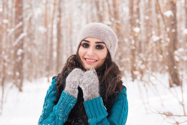 Portret van jonge mooie vrouw wandelen in het winter besneeuwde park op zonnige dag Premium Foto