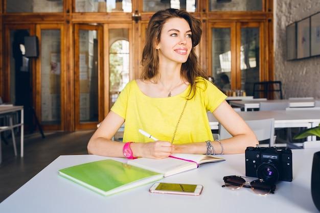 Portret van jonge mooie vrouw zitten aan tafel, student leren, onderwijs, glimlachen, notities schrijven in dagboek Gratis Foto