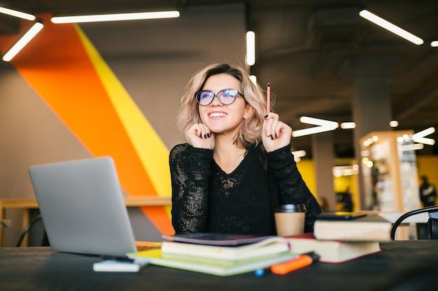 Portret van jonge mooie vrouw zittend aan tafel in zwart shirt bezig met laptop in co-working office Gratis Foto