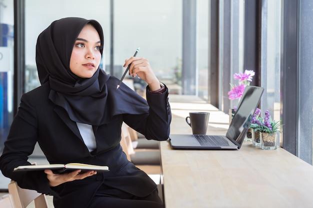 Portret van jonge moslim bedrijfsmensen die zwarte hijab dragen, die in koffie werken. Premium Foto