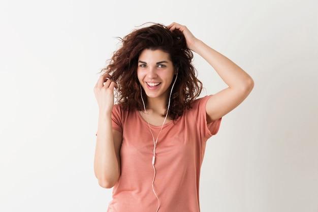 Portret van jonge natuurlijk ogende lachende gelukkig hipster mooie vrouw met krullend kapsel in roze shirt poseren geïsoleerd op witte studio achtergrond, luisteren naar muziek in oortelefoons Gratis Foto