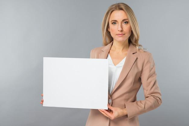 Portret van jonge onderneemster die leeg wit aanplakbiljet toont tegen grijze achtergrond Gratis Foto