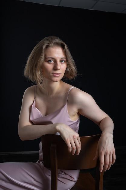 Portret van jonge peinzende blanke vrouw met kort haar poseren in roze pak, zittend op een stoel voor zwart. modelproeven van mooie dame in blouse, broek. aantrekkelijke vrouwelijke poses Premium Foto