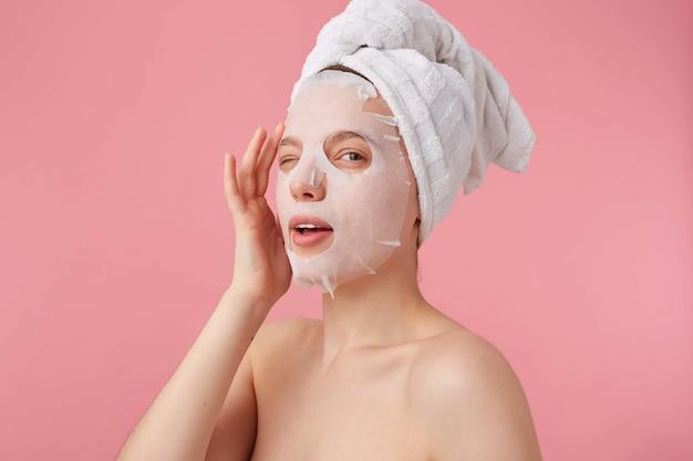 Portret van jonge positieve glimlachende vrouw na spa met een handdoek op haar hoofd, met masker voor gezicht, geniet van tijd voor zelfzorg, knipoogt, kijkt stands. Gratis Foto