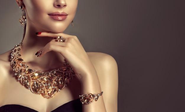 Portret van jonge prachtige vrouw gekleed in een sieraden set ketting, ring, armband en oorbellen. het vrij blauwogige model toont een aantrekkelijke make-up en een manicure aan. Premium Foto