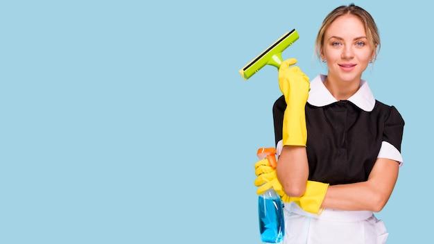 Portret van jonge schonere vrouw die plastic wisser en detergent fles houden bekijkend camera Gratis Foto