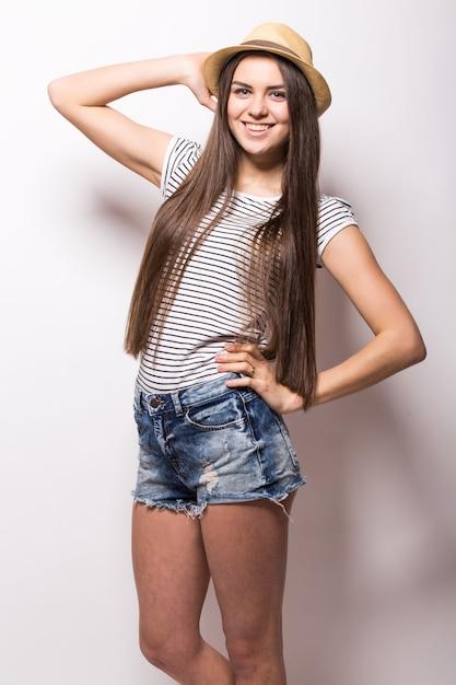 Portret van jonge trendy vrouw met spijkerbroek en strooien hoed, geïsoleerd op een witte muur Gratis Foto