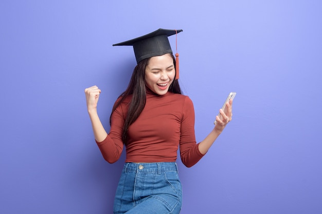 Portret van jonge universiteitsstudent vrouw met afstuderen cap op violet Premium Foto