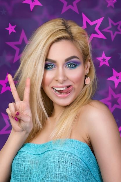 Portret van jonge vrolijke blonde vrouw die haar tong en overwinningsteken toont Premium Foto