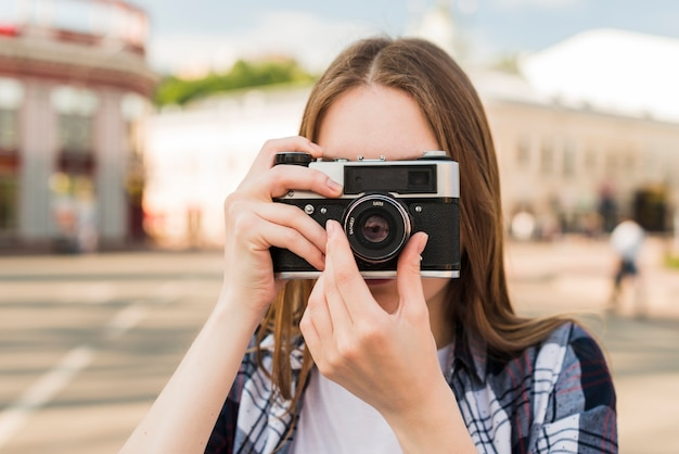 Portret van jonge vrouw die foto met camera neemt Gratis Foto