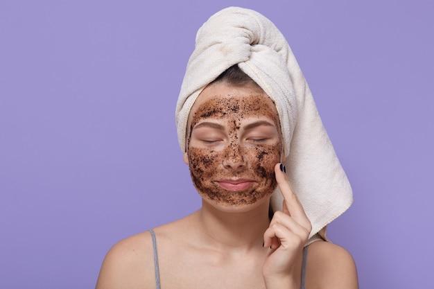 Portret van jonge vrouw past zelfgemaakte gezichts klei masker toe, heeft witte handdoek om het hoofd gewikkeld, de ogen gesloten Gratis Foto