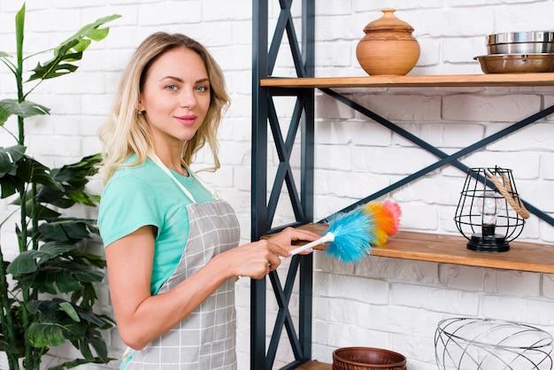 Portret van jonge vrouwelijke schonere schoonmakende planken met stofdoek Gratis Foto