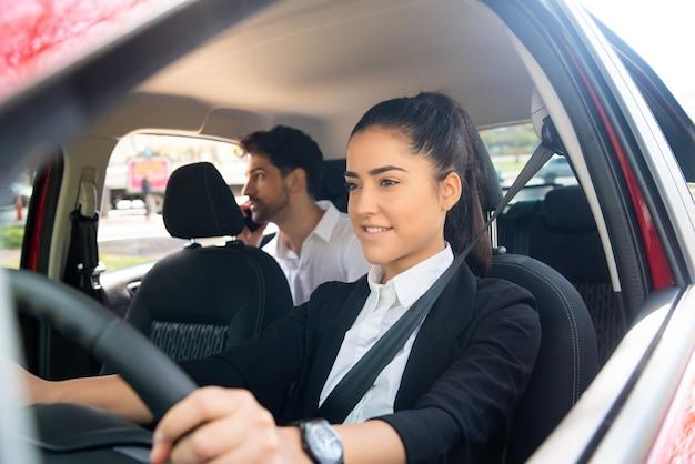 Portret van jonge vrouwelijke taxichauffeur met een zakenmanpassagier op achterbank. vervoer concept. Gratis Foto