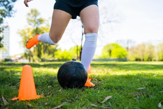 Portret van jonge vrouwelijke voetballer die kegels rondrennen terwijl het oefenen met bal op gebied. sport concept. Gratis Foto