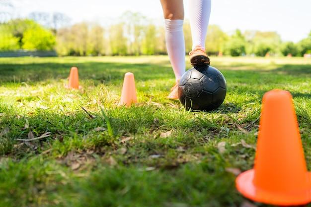 Portret van jonge vrouwelijke voetballer die kegels rondrennen tijdens het oefenen met de bal op het veld. sport concept. Premium Foto
