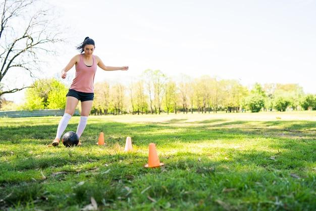 Portret van jonge vrouwelijke voetballer die kegels rondrennen tijdens het oefenen met de bal op het veld Gratis Foto