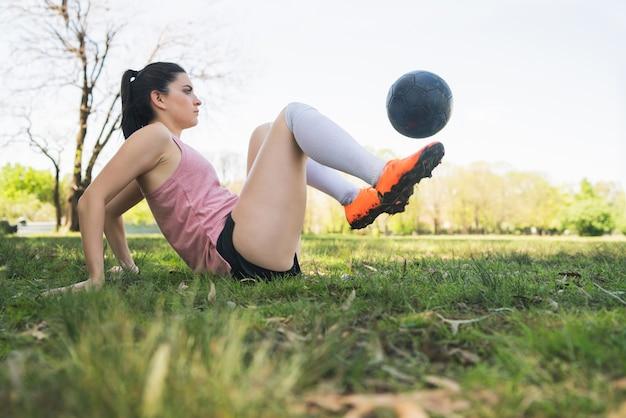 Portret van jonge vrouwelijke voetballer opleiding en het oefenen van vaardigheden op voetbalveld. sport concept. Premium Foto