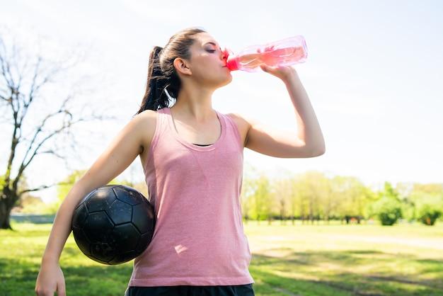 Portret van jonge vrouwelijke voetballer pauze op worp en drinkwater uit de fles Gratis Foto