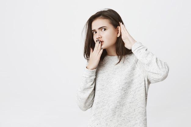 Portret van jonge vrouwelijke werknemer afluisteren of afluisteren iets, hand in hand in de buurt van mond en oor. Gratis Foto