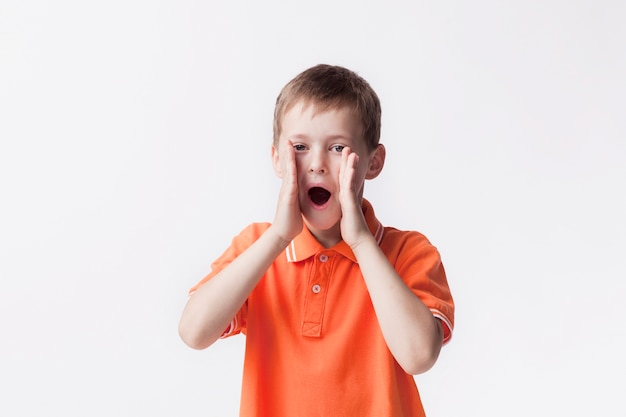 Portret van jongen die met mond open status gilt dichtbij witte muur Gratis Foto