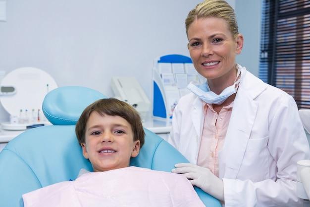 Portret van jongen zittend op een stoel door tandarts Premium Foto