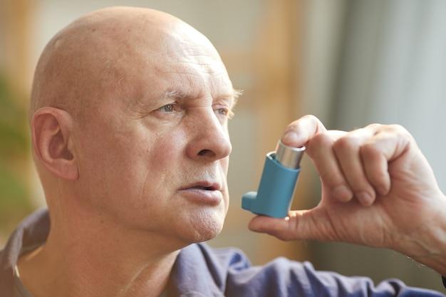 Portret van kale senior man met inhalator voor astma of ademhalingsproblemen in interieur Premium Foto