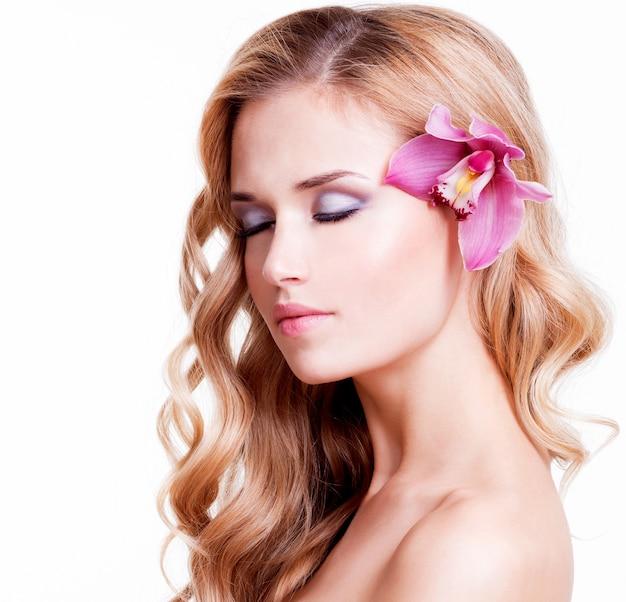 Portret van kalm mooi meisje met roze orchidee in haar haar - geïsoleerd op wit. Gratis Foto