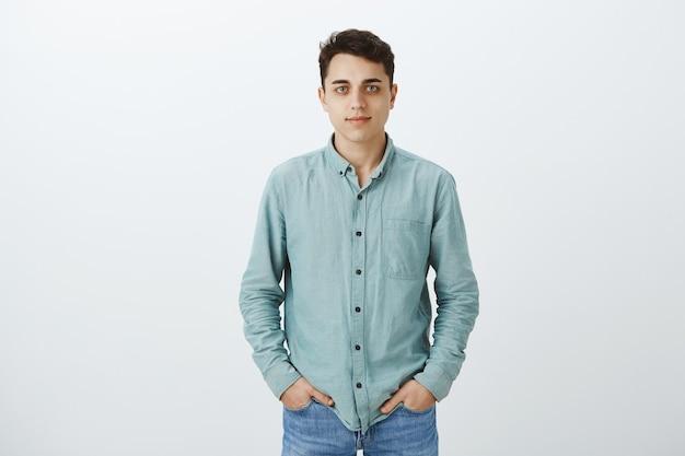Portret van kalme knappe mannelijke universiteitsstudent in casual overhemd Gratis Foto