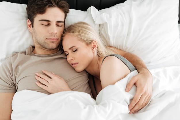 Portret van kalme knappe paarslaap in bed Gratis Foto