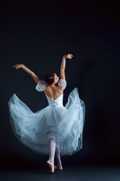 Portret van klassieke ballerina in witte jurk op zwart Gratis Foto