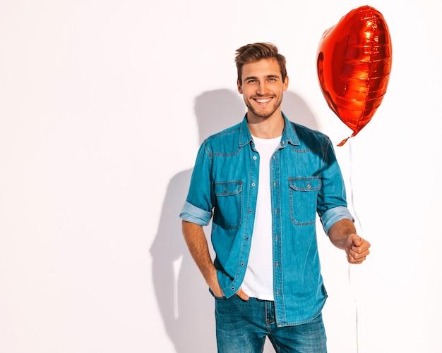 Portret van knap glimlachend modieus mensenmodel gekleed in jeanskleren. mode man met hartvormige ballon. Gratis Foto